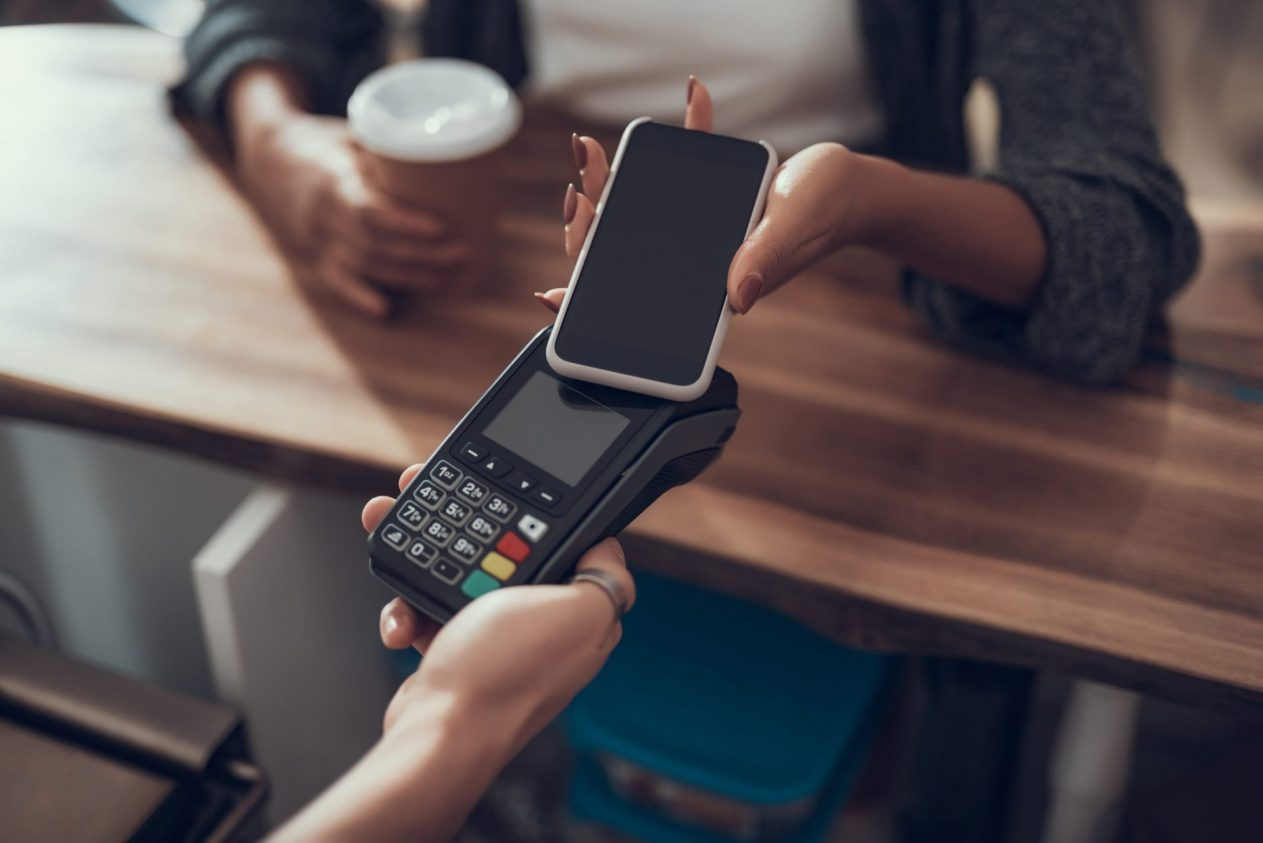Contactless payment. Progressive lady with manicure standing at the bar counter and paying with her phone